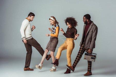 Photo pour Amis de style rétro multiculturel dansant avec radio vintage sur gris - image libre de droit