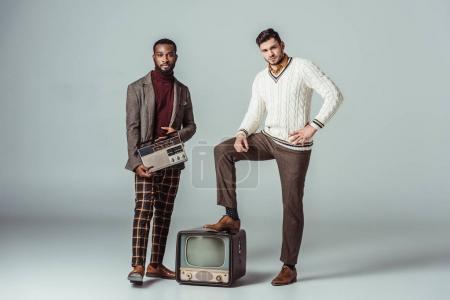 Photo pour Multicultural rétro style amis posant avec vintage radio et la télévision sur fond gris - image libre de droit