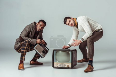 multicultural retro styled friends squatting with vintage radio and television on grey