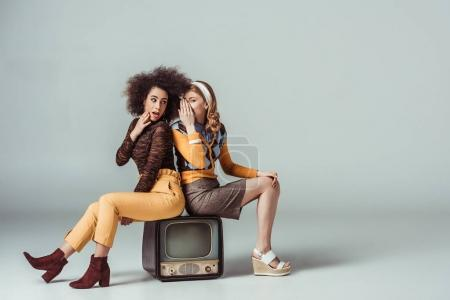 Photo for Multicultural retro styled girls gossiping and sitting on vintage television - Royalty Free Image