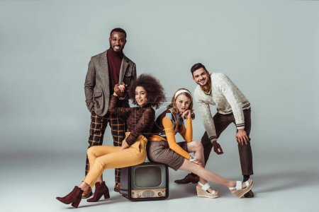 multicultural retro styled friends posing with vintage television on grey