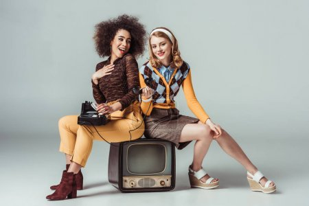 Photo for Happy multicultural retro styled girls sitting on vintage television with stationary telephone - Royalty Free Image