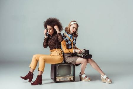 Photo for Multicultural retro styled girls sitting on old tv and talking by stationary telephone - Royalty Free Image