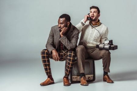 Foto de Multicultural retro estilo a amigos sentado en la vieja televisión y hablar por teléfono fijo - Imagen libre de derechos