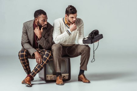 Photo for Multicultural retro styled friends sitting on vintage television and looking at stationary telephone - Royalty Free Image