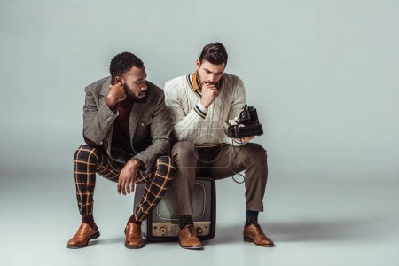 Photo for Multicultural retro styled friends sitting on vintage television and holding stationary telephone - Royalty Free Image
