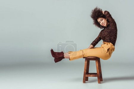 Photo for Side view of african american woman in retro clothes sitting on chair on grey - Royalty Free Image