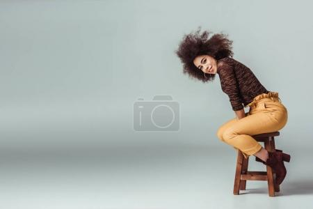 attractive african american woman in retro clothes sitting on chair on grey