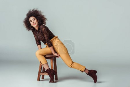 Photo for Smiling african american girl in retro clothes sitting on wooden chair on grey - Royalty Free Image