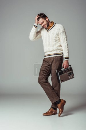 smiling retro styled handsome man with vintage radio on grey