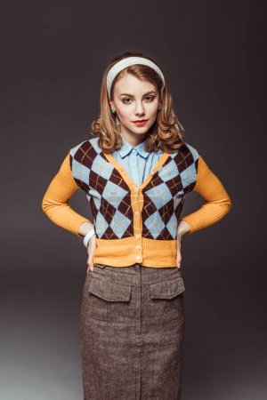 attractive retro styled girl looking at camera with hands akimbo isolated on grey