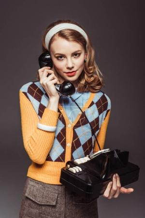 Photo for Attractive retro styled girl talking by vintage stationary telephone isolated on grey - Royalty Free Image