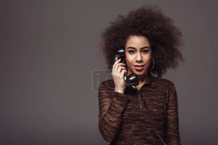 african american retro styled girl talking by vintage stationary telephone isolated on grey