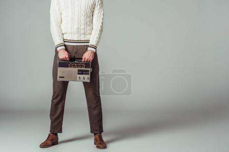 Photo for Cropped image of retro styled man holding vintage radio on grey - Royalty Free Image