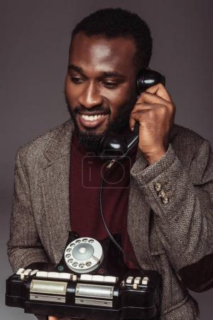 smiling african american retro styled man talking by vintage stationary telephone isolated on grey