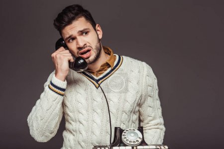irritated retro styled handsome man talking by vintage stationary telephone isolated on grey