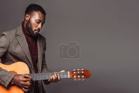 african american retro styled guitarist playing acoustic guitar isolated on grey