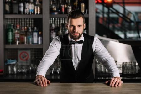 Photo pour Beau barman appuyé sur le comptoir du bar et regardant la caméra - image libre de droit