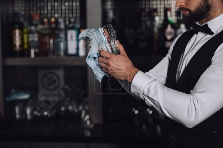 cropped image of bartender cleaning glass with rag in evening