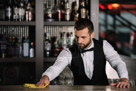 handsome bartender cleaning bar counter in evening