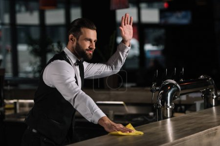 handsome bartender cleaning bar counter and waving hand to someone