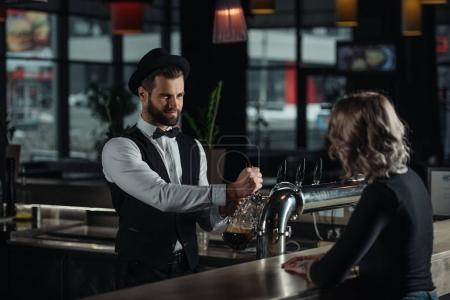 smiling bartender pouring beer from beer taps into glass and looking at visitor
