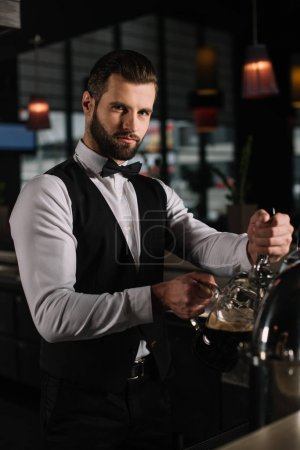 handsome bartender pouring beer from beer taps into glass and looking at camera