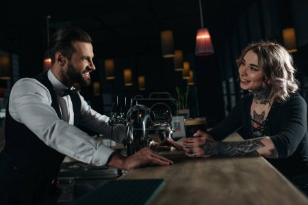 side view of smiling male bartender and girl looking at each other at bar counter