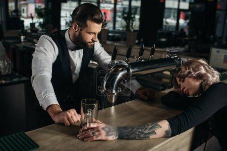 bartender looking at drunk girl sleeping at bar counter