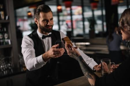 visitor giving credit card to bartender to pay for drinks