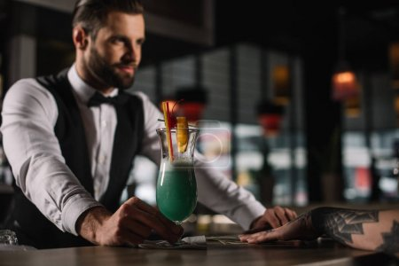 handsome bartender giving alcohol drink to girl at bar counter