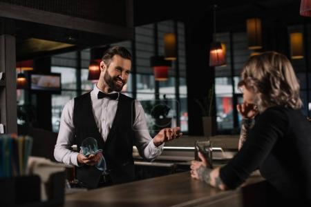 smiling bartender cleaning glass and talking with female visitor