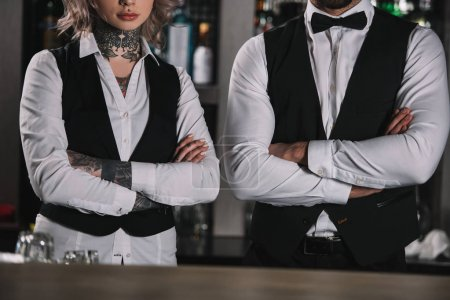 Photo for Cropped image of female and male bartenders standing with crossed arms at bar - Royalty Free Image