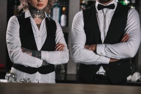 Photo pour Image recadrée de barmans féminins et masculins debout avec des bras croisés au bar - image libre de droit