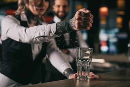 Photo for Tattooed bartender squeezing out lemon juice into glass at bar - Royalty Free Image