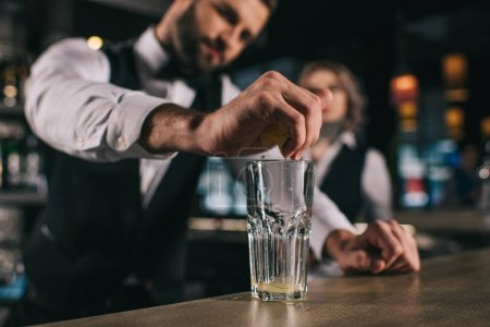 Photo for Male bartender squeezing out lemon juice into glass at bar - Royalty Free Image