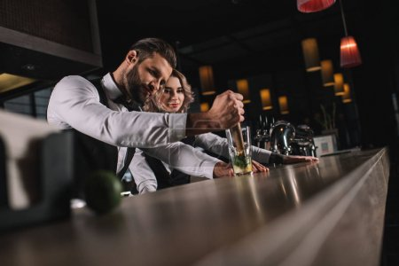 male bartender showing colleague how to prepare drink at bar