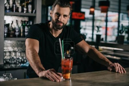 Photo for Handsome barman standing with alcohol drink at bar counter - Royalty Free Image