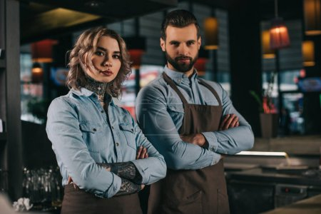 Photo for Bartenders standing with crossed arms and looking at camera at bar - Royalty Free Image