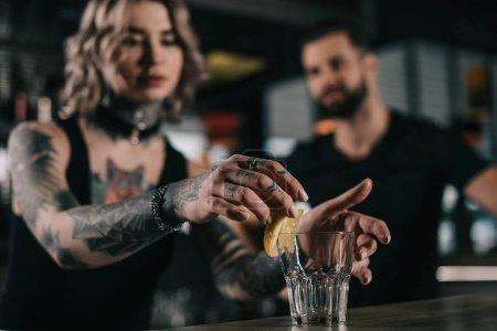 Photo pour Barman mettre un morceau de citron dans le verre au bar - image libre de droit