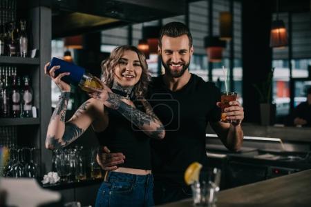 smiling young bartenders preparing alcohol drinks at bar and looking at camera