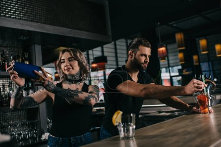 young bartenders preparing alcohol drinks at bar