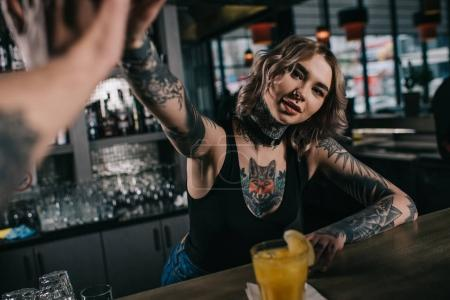 cropped image of tattooed bartender giving high five to visitor at bar