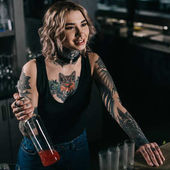 tattooed bartender holding bottle of alcohol and looking away