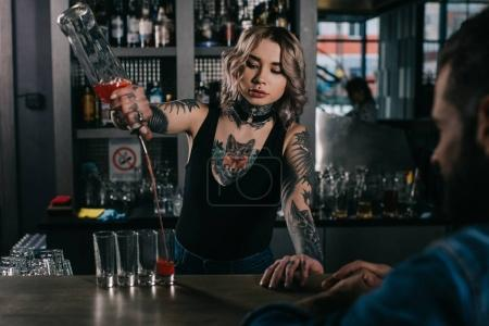 tattooed bartender making shot drinks for man at bar
