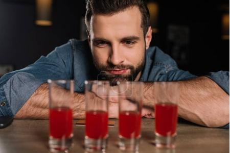handsome visitor sitting at bar counter and looking at four shot drinks
