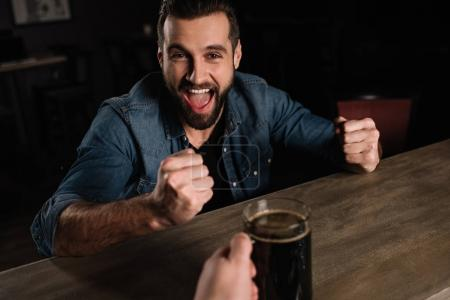 bartender giving beer to visitor and he showing yes gesture