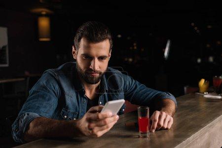 visitor sitting at bar counter and looking at smartphone