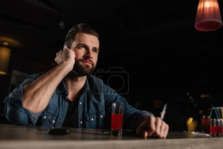 visitor sitting at bar counter and talking by smartphone