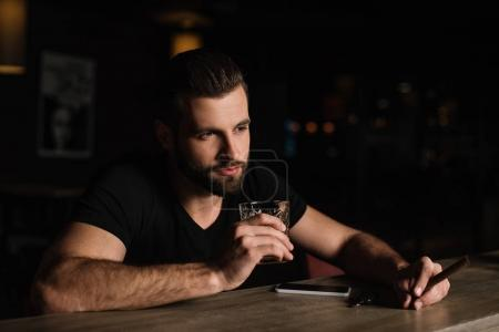 handsome visitor sitting at bar counter and holding glass of whiskey and cigar